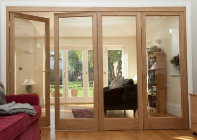Internal wooden bifold doors with a light stain finish at a property in Kingston upon Thames